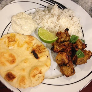 Plate of tandoori chicken, naan, basmati rice and cucumber raita