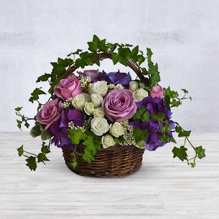 Description: During these though times it is important to pay tribute to a life well lived. This beautiful basket of white and purple flowers highlighted with eye-catching greenery is the perfect way to celebrate and remember the lives of those closest to you. *This item is available for same day delivery only if ordered before 1 pm EST* Orientation: All-AroundDimensions: Approx. 16 3/4 W x 12 1/2 H Arrangement Details: Brilliant flowers such as purple hydrangea, lavender roses, white spray roses and waxflower are arranged with beautiful ivy and more in a lovely round basket.